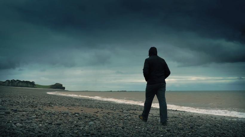 man-walks-alone-on-windswept-beach_myzavvfr__F0000
